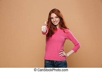 Portrait of a young smiling redhead girl looking at camera