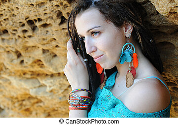 Portrait of a young smiling woman wearing dreadlocks hairstyle, dressed in blue lace dress and blue boho chic earrings