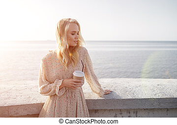 Portrait of a young smiling woman with coffee outdoor near the sea