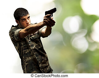 soldier aiming - portrait of a young soldier aiming with...