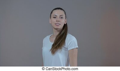 Portrait of a young sport model, which is smiling. In the studio on a gray background. Slow motion.