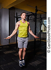 Portrait of a young sportsman in the sportwear skipping with...