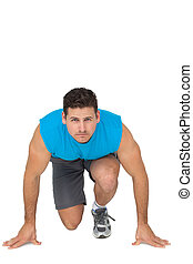 Portrait of a young sporty man in running stance