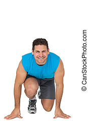 Portrait of a young sporty smiling man in running stance