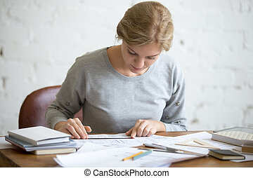 Portrait of a young student girl at desk