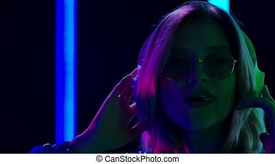 Portrait of a young stylish woman in sunglasses dancing to the music with big white headphones and chewing gum. Blonde with pink short hair poses against a dark studio background with bright multicolored neon lights. Close up. Slow motion.