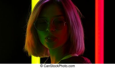 Portrait of a young stylish woman in sunglasses looking at the camera chewing gum and blowing bubbles. Blonde with pink short hair poses against a dark studio background with bright multicolored neon lights. Close up. Slow motion.