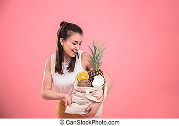 Portrait of a young stylish woman with an eco-fruit bag.