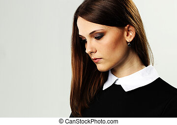 Portrait of a young thoughtful woman on gray background