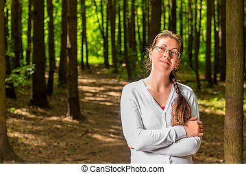 Portrait of a young thoughtful woman with glasses in forest