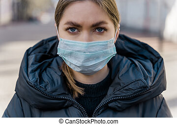 Pandemic, portrait of a young tourist woman wearing protective mask on street