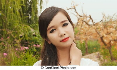 Portrait of a young vietnamese asian girl looking at camera. Strong makeup.