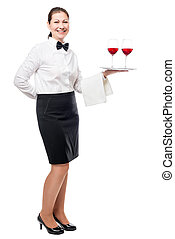 Portrait of a young waitress with glasses of red wine on a tray isolated in full length