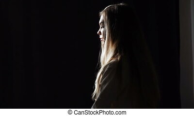 Portrait of a young woman against dark background. Studio shot with low key lighting