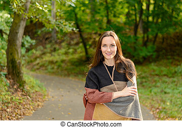 Portrait of a young woman brunette in a wool poncho Standing on a footpath in the green Park in the background in the rays of the bright sun