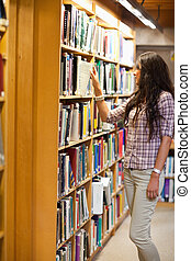 Portrait of a young woman choosing a book in a library