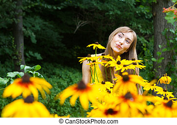 Portrait of a young woman close up in the woods with flowers