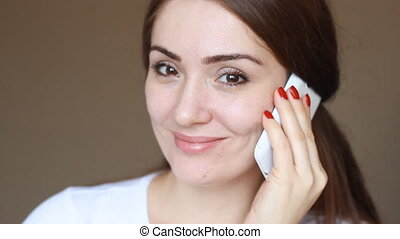 Portrait of a young woman close-up who talks on her mobile phone, agrees, smiles and looks at the camera.