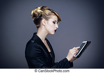 Portrait of a young woman consulting her tablet computer