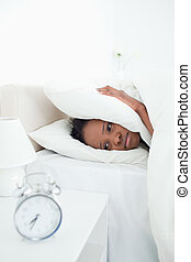 Portrait of a young woman covering her ears while her alarm clock is ringing in her bedroom