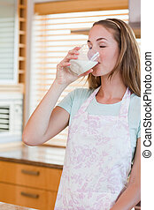 Portrait of a young woman drinking a glass of milk