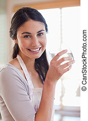 Portrait of a young woman drinking water