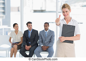 Portrait of a young woman gesturing thumbs up with people waiting for job interview in a bright office