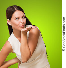 Portrait Of A Young Woman Giving Flying Kiss against a green...