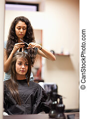 Portrait of a young woman having a haircut looking away from...
