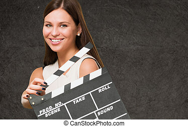 Portrait Of A Young Woman Holding Clapboard against a grunge...