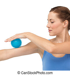Portrait of a young woman holding stress ball on arm over ...