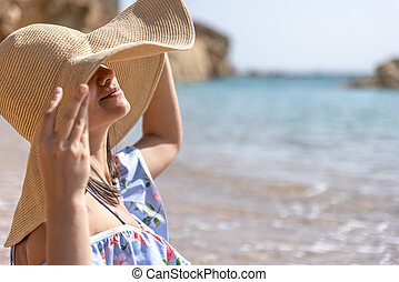 Portrait of a young woman in a big hat on the beach.