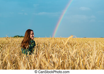 Portrait of a young woman in a field with wheat ears on a rainbow background