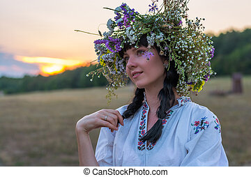 Portrait of a young woman in a long white embroidered shirt and in a wreath of wild flowers stands in the field at sunset.