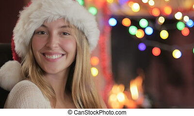 Portrait of a young woman in a Santa hat motioning come here with her finger