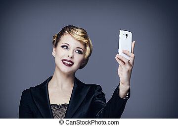 Portrait of a young woman in business suit, taking a photo with her mobile phone