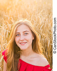 Portrait of a young woman in red dress on a background of golden oats field, summer outdoors