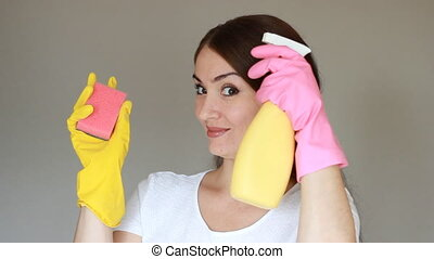 Portrait of a young woman in rubber gloves looks at the...
