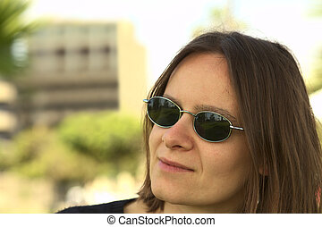 Portrait of a young woman in sunglasses with a building and trees in the background (Selective Focus, Focus on the left eyebrow and sunglasses)