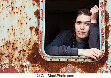 Portrait of a young woman in the window of an abandoned industrial facility.