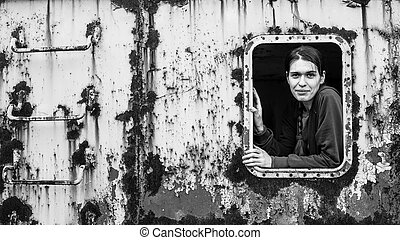Portrait of a young woman in the window of an abandoned iron rusty object. Black and white photo.