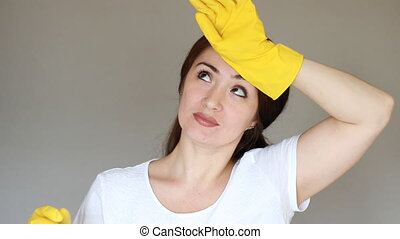 Portrait of a young woman in yellow rubber gloves looks at the camera smiling and expresses fatigue. The concept of cleaning, cleanliness