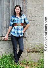 young woman leaning on barn