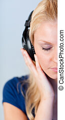 Portrait of a young woman listening music with headphones and closed eyes