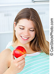 young woman looking at an apple