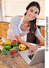 Portrait of a young woman looking for a recipe on the internet