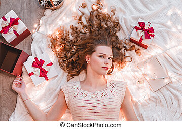 Portrait of a young woman lying on white plaid with christmas gifts