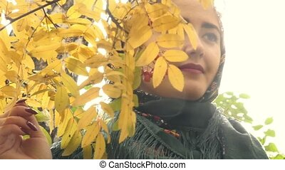 Portrait of a young woman on a background of yellow leaves of mountain ash in an autumn park