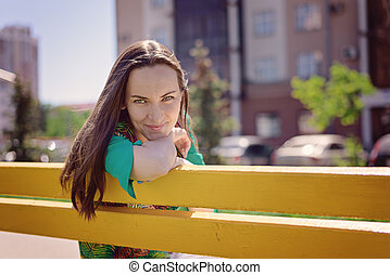 Portrait of a young woman on a yellow bench, smiling looking at the camera, copy space