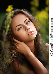 Portrait of a young woman on flowers field